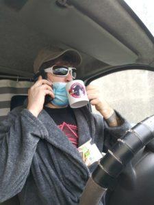 Automobiliste qui téléphone au volant en buvant du café